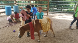 children decorating miniature horse