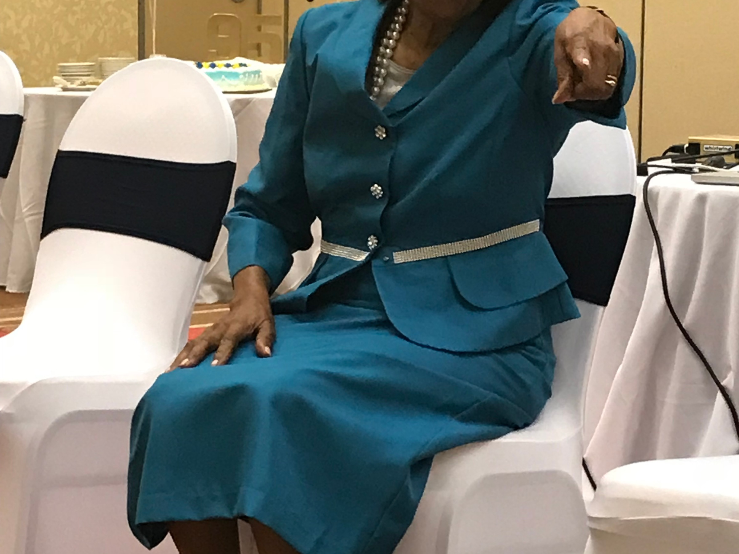 Margaret McCormick sitting in chair, in turquoise skirt suit. She's pointing at the camera and has a smirk on her face. It's her birthday.