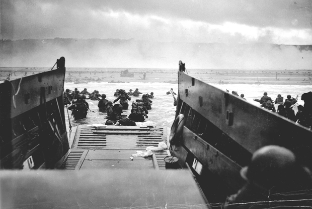 Soldiers leaving a boat and in the water of Omaha Beach, Normandy, during World War II.
