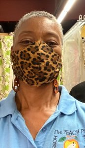 Woman in leopard print covering her nose and mouth.